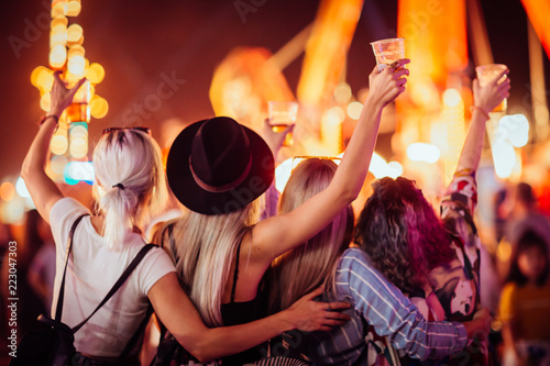 Back view of group of female friends at music festival drinking beer and dancing