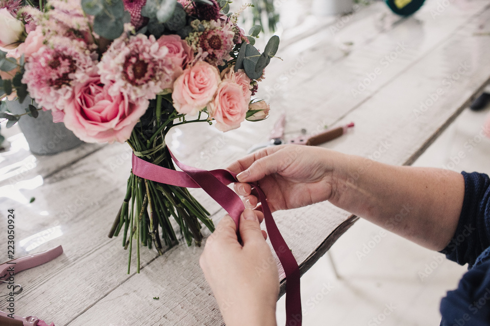 Fototapeta hands of a florist bandage a bouquet with a pink ribbon