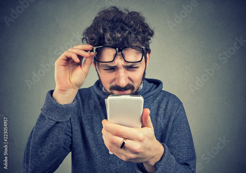 Fotografia man wearing glasses having trouble seeing cell phone message