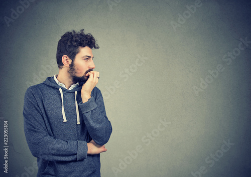 Stampa su Tela  Preoccupied anxious man biting his fingernails