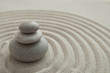 Pyramids of gray zen stones on the sand with wave drawings. Concept of harmony, balance and meditation, spa, massage, relax