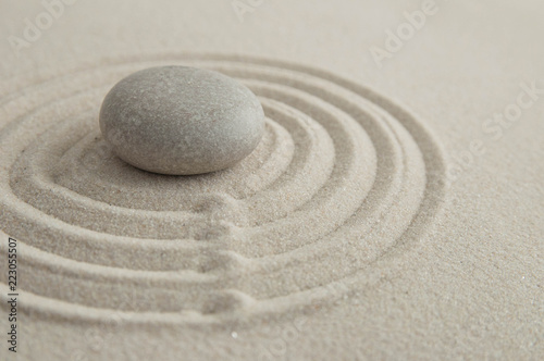 Photo sur Plexiglas Zen pierres a sable Pyramids of gray zen stones on the sand with wave drawings. Concept of harmony, balance and meditation, spa, massage, relax
