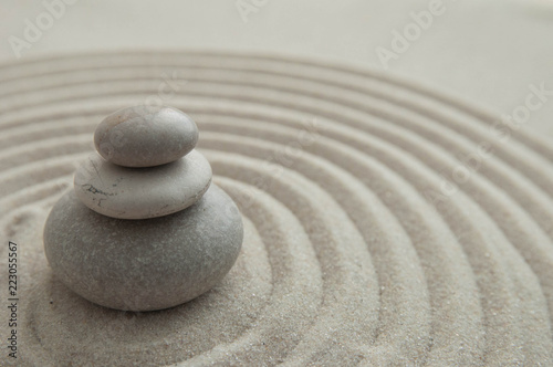 Foto op Aluminium Stenen in het Zand Pyramids of gray zen stones on the sand with wave drawings. Concept of harmony, balance and meditation, spa, massage, relax