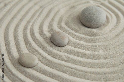 Staande foto Stenen in het Zand Pyramids of gray zen stones on the sand with wave drawings. Concept of harmony, balance and meditation, spa, massage, relax