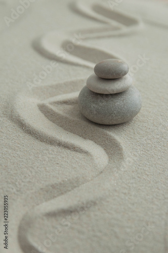 Tuinposter Zen Pyramids of gray zen stones on the sand with wave drawings. Concept of harmony, balance and meditation, spa, massage, relax