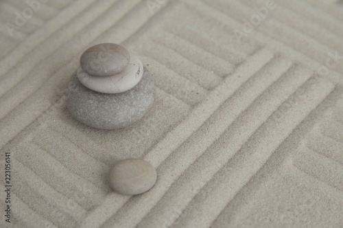 Foto op Canvas Zen Pyramids of gray zen stones on the sand with wave drawings. Concept of harmony, balance and meditation, spa, massage, relax