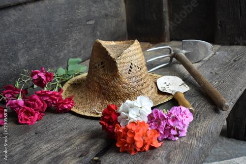 Fotografija  Sombrero de mimbre, flores recien cortadas y herramienta de jardinero