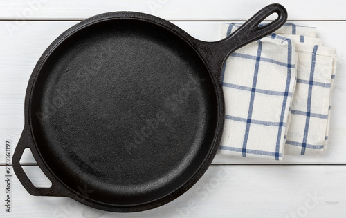 Empty, clean black cast iron pan or dutch oven top view from above on white table with towel