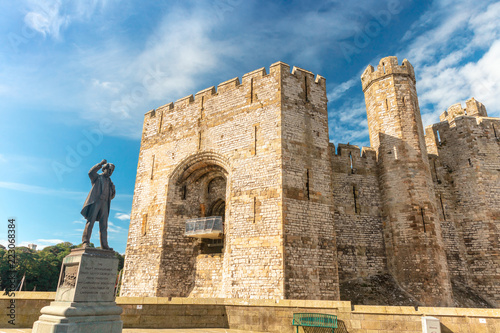Photo  Caernarfon Castle in North Wales with bronze statue of David Lloyd George Prime Minister of the United Kingdom, 1916-22