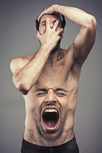 Tortured Man, Pain And Insanity Concept: Man Screaming With Face Covered, His Abdomen Showing His Face Screaming And Yelling