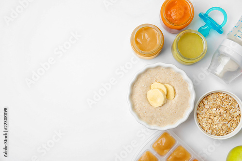 Flat lay composition with bowl of healthy baby food and space for text on white background