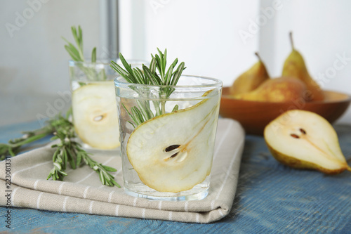 Refreshing pear cocktail with rosemary on table