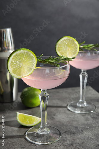 Tasty refreshing lime cocktail with rosemary on table