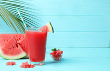 Summer Watermelon Drink In Glass And Sliced Fruit On Table Against Color Background With Space For Text