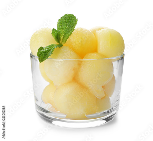 Glass with melon balls on white background