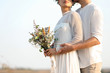 Happy newlyweds with beautiful field bouquet outdoors, closeup