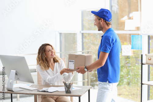 Fotografia  Young woman receiving parcel from courier in office