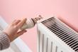 Leinwandbild Motiv Woman adjusting heating radiator near color wall