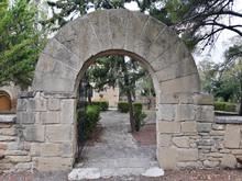 Front View Of Stone Door With Arch Shaped Exterior. Door Open