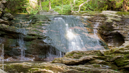 Poster Watervallen Summer waterfall on an old stone cover with moss in the Regional Park of the province of Quebec, Canada. - Long Exposure Photo