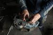 The mechanic serves the truck. Repair brake caliper. Close-up. Maintenance. Brake system. Brake spare parts. Hands working close-up.