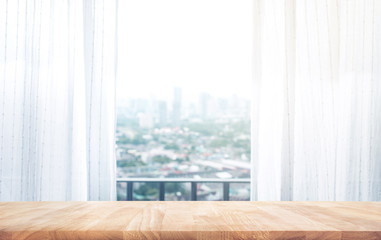 Wood table top on on blur of curtain with window city view background