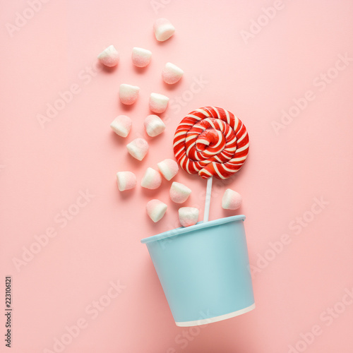 Poster Confiserie Sweet basket / Creative concept photo of candies in basket on pink background.