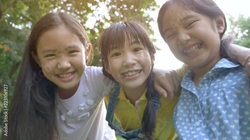 Group of little happy Asian girls playing together in the park Canvas Print