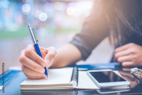Fényképezés  Woman hand writing on a notebook.with a pen.