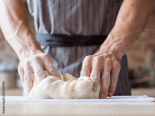 In de dag Bakkerij bakery and homemade bread. food preparing and cooking skills concept. man hands kneading dough.