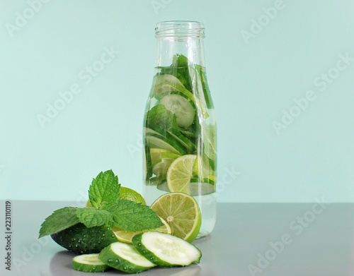 Infused detox water with mint, cucumber, lime, recipe for weight loss, gray mint background, space for text.