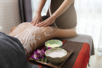 Obraz na płótnie Canvas Spa therapist applying scrub salt and cream on young woman back at salon spa. Hands massaging female back with scrub.