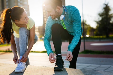 Fototapeta Young fitness couple running in urban area