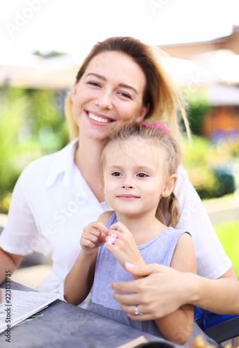 Fotografía  Caucasian blonde young mother sitting with little female child outside and smiling