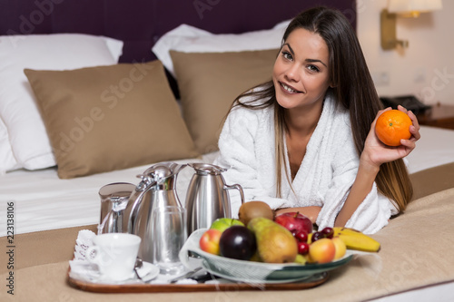 Relaxing woman on bed with fruit