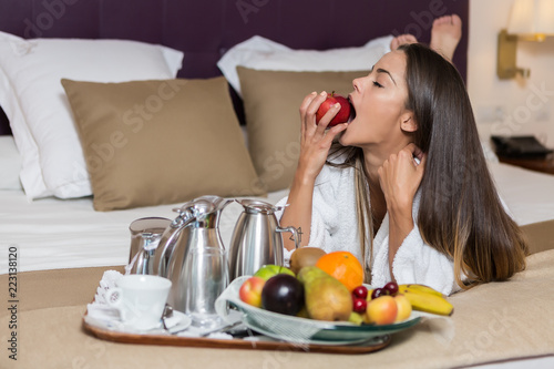 Sensual woman eating apple on hotel bed