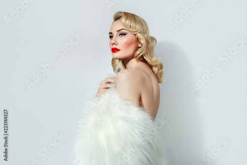 Photo  Portrait of a beautiful young girl with blond wavy hair and with red lips and black arrows in retro style