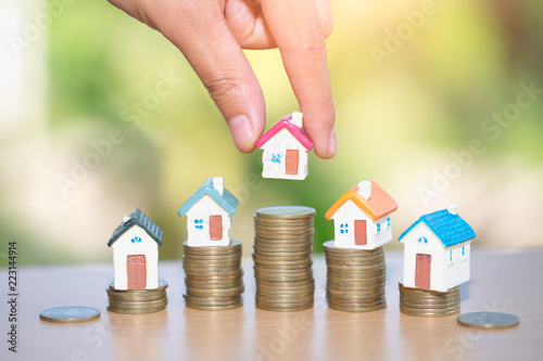 Fototapeta Mini house on stack of coins, Real estate investment, Save money with stack coin, Business growth investment and financial, Mortgage concept. obraz