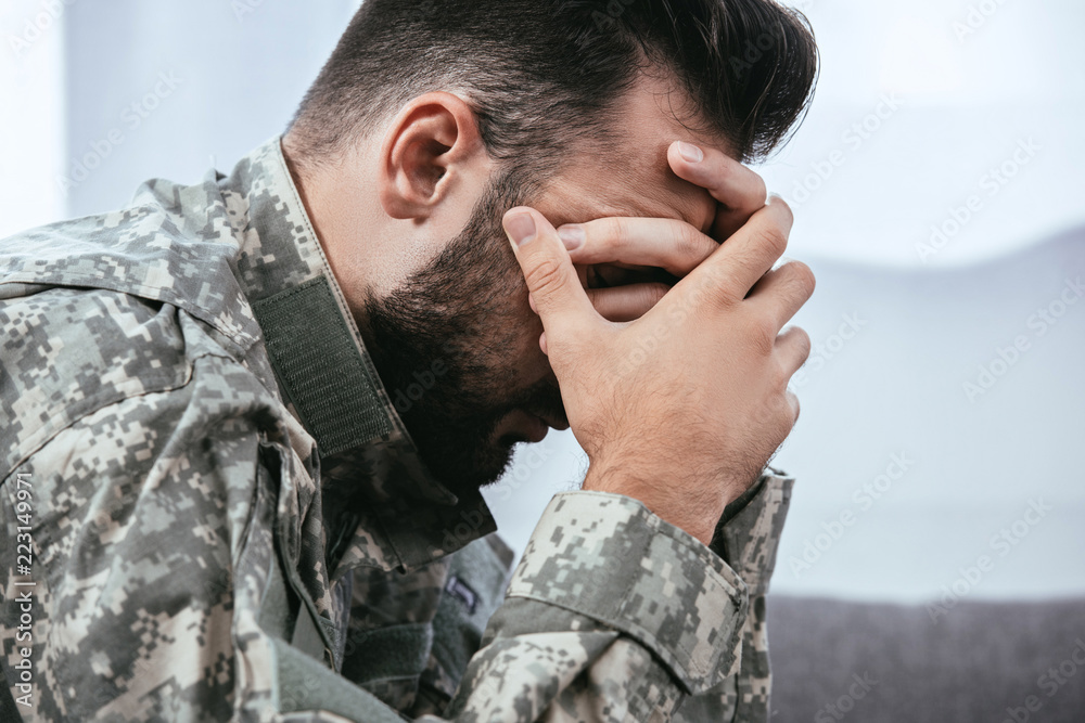 Fototapeta side view of depressed army man in military uniform with post-traumatic stress disorder holding his head
