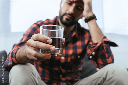 Poster Bar close-up shot of depressed young man with glass of whiskey