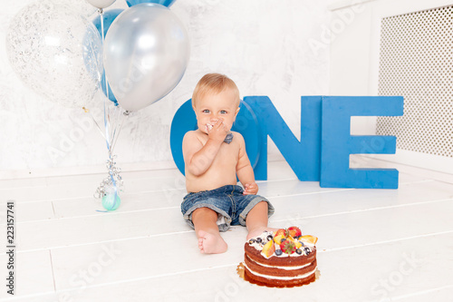 Portrait of fashion funny little boy in studio with big blue letters, balloons and cake