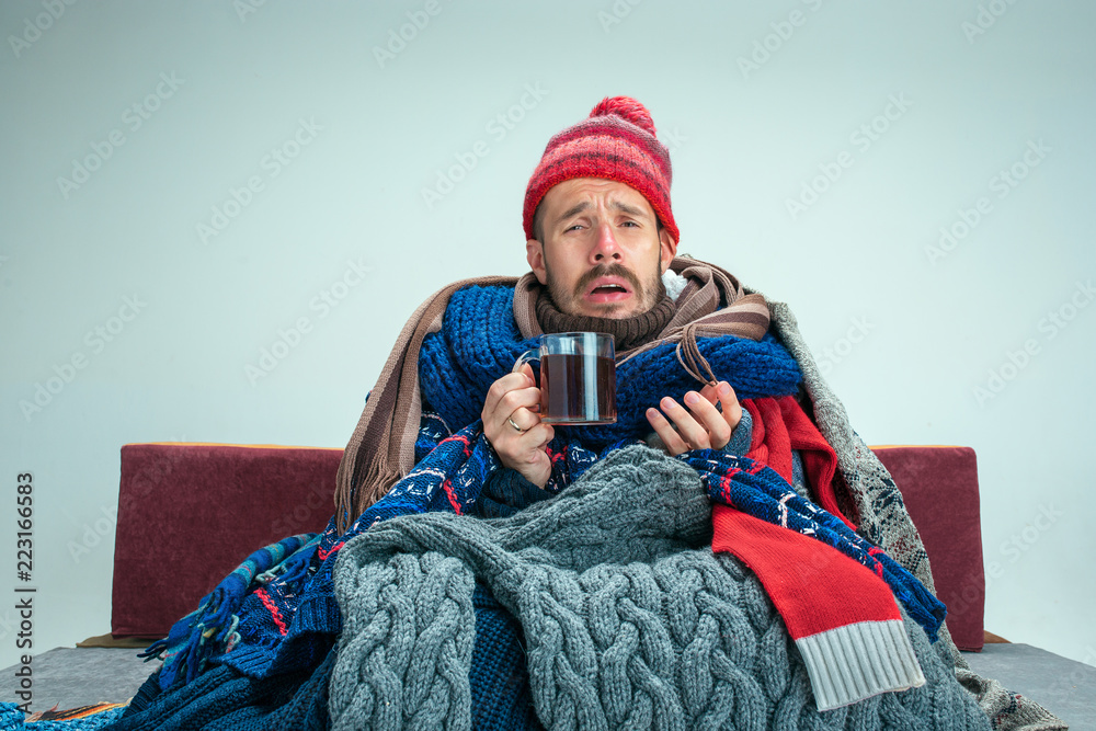 Fototapeta Bearded sick man with flue sitting on sofa at home or studio with cup of tea covered with knitted warm clothes. Illness, influenza concept. Relaxation at Home. Healthcare Concepts.