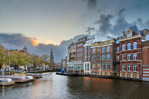 Staande foto Amsterdam Beautiful cityscape view towards the Mint tower (Munttoren) with tourist canal boats at the Amstel river in Amsterdam, the Netherlands, with ominous clouds around sunset