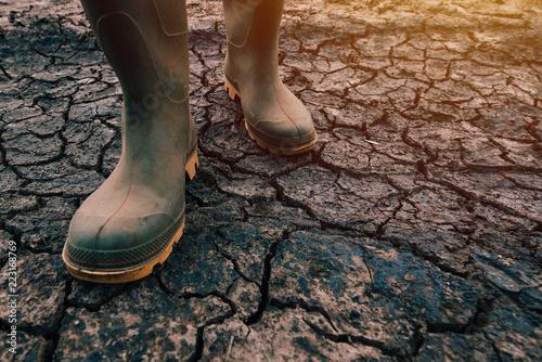 Fotografia Farmer in rubber boots walking on dry soil ground