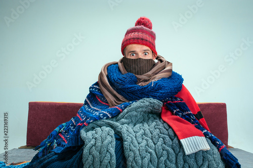 Obraz Bearded sick man with flue sitting on sofa at home or studio covered with knitted warm clothes. Illness, influenza, pain concept. Relaxation at Home. Healthcare Concepts. - fototapety do salonu