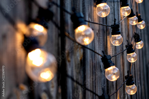Photo  Lots of warm LED light bulbs on old wooden background in the garden, copyspace,