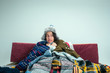 Leinwanddruck Bild - The young sick woman with flue sitting on sofa at home or studio covered with knitted warm clothes. Illness, influenza, pain concept. Relaxation at Home. Healthcare Concepts.