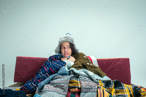 The young sick woman with flue sitting on sofa at home or studio covered with knitted warm clothes Wallpaper Mural