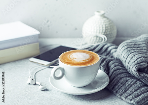 Leinwand Poster Cup of cappuccino coffee, a warm gray cloth, a smart phone and books on gray background