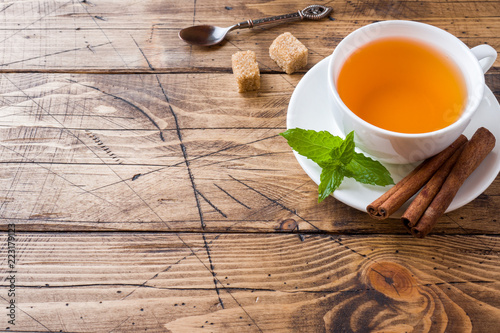 Staande foto Thee Cup of hot tea with mint and brown sugar on a wooden table Copy sapce
